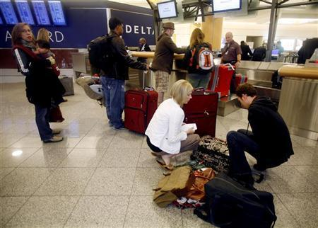 Holiday travelers check their bags at a Delta counter as they prepare for Thanksgiving holiday travel at Hartsfield-Jackson International Airport in Atlanta, Georgia November 25 , 2009. REUTERS/Tami Chappell