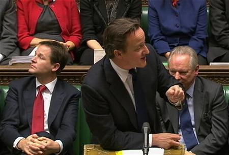 Britain's Prime Minister David Cameron (R) addresses parliament next to Deputy Prime Minister Nick Clegg during the weekly Prime Minister's Questions session in London December 14, 2011.   REUTERS/Parbul TV via Reuters TV