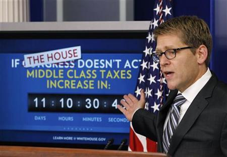 White House Press Secretary Jay Carney points to a payroll tax cut extension countdown monitor in the briefing room of the White House in Washington December 20, 2011. REUTERS/Jason Reed