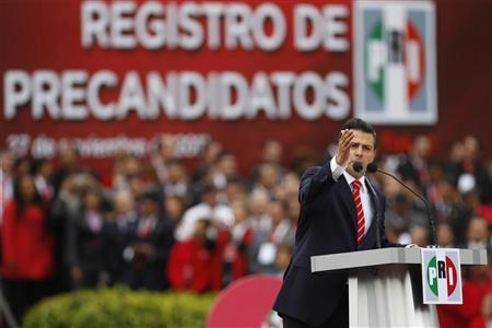 Enrique Pena Nieto, former Mexico state governor and a presidential candidate for the Institutional Revolutionary Party (PRI), delivers a speech to his supporters on stage after filing for candidacy for his party in Mexico City November 27, 2011. REUTERS/Carlos Jasso