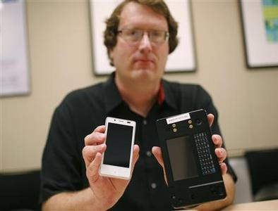 Mike Bell, co-general manager of Intel's new Mobile and Communications Group, holds an Android reference smartphone (L) he designed, next to a reference phone Intel used to demonstrate the chip at earlier stages, during an interview at the company's headquarters in Santa Clara, California December 20, 2011.   REUTERS/Robert Galbraith