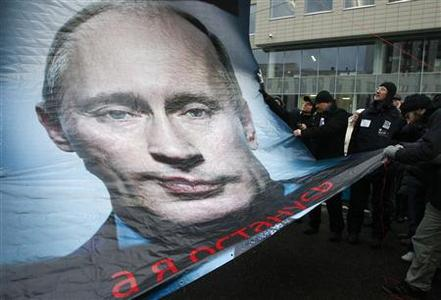 Protesters hold a banner with a portrait of Russian Prime Minister Vladimir Putin during a demonstration against recent parliamentary election results in Moscow December 24, 2011. The words read, ''But I'm staying''.  REUTERS/Mikhail Voskresensky