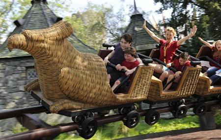 Harry Potter film star Daniel Radcliffe rides the Flight of the Hippogriff attraction at Universal Orlando Resort in Florida June 18, 2010 with some of the first guests to the new spectacularly themed area. Photo taken June 18, 2010.   REUTERS/Kevin Kolczynski-Universal Orlando/HO