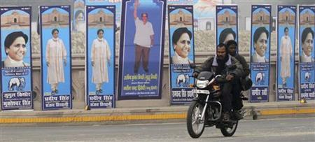 Men on a motorcycle ride past pictures of Dalit icon Kanshi Ram (C) and Mayawati, the chief minister of of Uttar Pradesh, on the eve of an election campaign rally, to be addressed by Mayawati, for next year's state elections in Lucknow December 17, 2011. REUTERS/Pawan Kumar