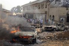 Горящая машина на месте взрыва бомбы возле Церкви Святой Терезы в Мадалле 25 декабря 2011 года. По меньшей мере 27 человек погибли в Нигерии в Рождество в результате взрывов, организованных исламистами. REUTERS/Afolabi Sotunde