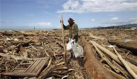 A man gathers wood amidst logs and debris washed ashore after Typhoon Washi hit a village in Iligan city, southern Philippines December 20, 2011. REUTERS/Erik De Castro