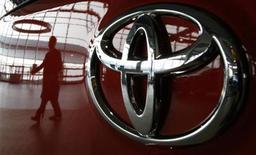 Отражение посетителя салона Toyota в Токио на капоте автомобиля. Фотография сделана 17 июня 2011 года. Toyota Motor Corp представила в понедельник новый автомобиль с гибридным двигателем, потребляющим топлива меньше, чем любая другая машина этого типа. REUTERS/Toru Hanai