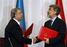 Министр энергетики Турции Танер Йылдыз (справа) жмет руку своему азербайджанскому коллеге Натику Алиеву в Стамбуле 7 июня 2010 года. Трансанатолийский газопровод, по которому азербайджанский газ будет поступать в Европу через Турцию, обойдется примерно в $5 миллиардов и будет иметь пропускную способность 35 миллиардов кубометров в год, сообщили в понедельник министры энергетики Турции и Азербайджана. REUTERS/Murad Sezer