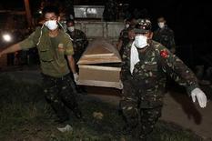 """Солдаты несут гроб с телом погибшего в результате тайфуна """"Ваши"""" во время массовой церемонии захоронения в филиппинском городе Илиган 20 декабря 2011 года. Число погибших на Филиппинах в результате одного из худших стихийных бедствий в стране за последние двадцать лет выросло до 1.249, около 1.100 человек пропали без вести, сообщили власти в понедельник. REUTERS/Erik De Castro"""