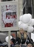 """Протестующие держат в руках табличку с надписью """"До свидания, Путин!"""" на английском языке на демонстрации в Москве 24 декабря 2011 года. Владимир Путин, похоже, все больше теряет связь с обществом после крупнейшего за время его правления выступления оппозиции, собравшего в минувшую субботу десятки тысяч недовольных режимом. Их требованием, как и две недели назад, было признание результатов выборов в Госдуму 4 декабря недействительными. REUTERS/Tatyana Makeyeva"""