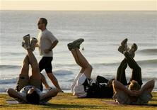 <p>A jogger (2nd L) passes fitness enthusiasts performing stretching exercises after sunrise at Queenscliff Beach in Sydney on the first day of Spring September 1, 2008. REUTERS/Will Burgess</p>