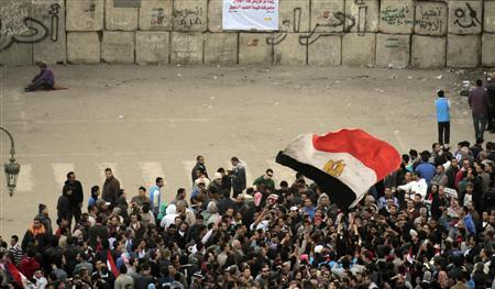 Protesters against the military council stand in front of a barricade placed by the Egyptian military next to a building near cabinet offices to separate Egyptian military and riot police from protesters near Tahrir Square in Cairo December 23, 2011. REUTERS/Amr Abdallah Dalsh