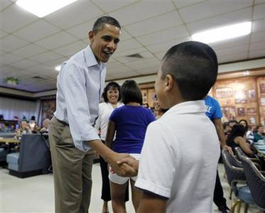 U.S. President Barack Obama greets a young boy as he meets with U.S. Marines and their families having Christmas lunch at Kaneohe Bay Marine Corps base, December 25, 2011. REUTERS/Jason Reed