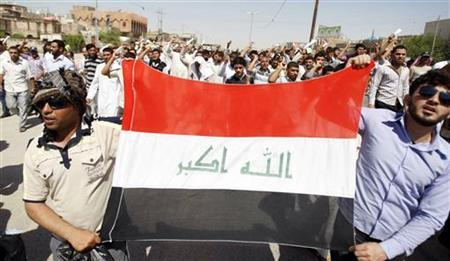Supporters of Iraqi Shi'ite cleric Moqtada al-Sadr hold their national flag during a demonstration in Basra, 420 km (260 miles) southeast of Baghdad, September 16, 2011. REUTERS/Atef Hassan