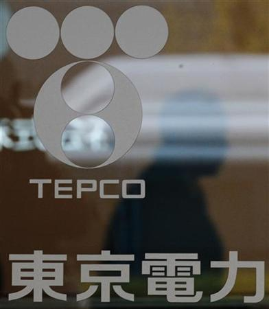 The silhouette of a visitor is seen behind the logo of Tepco, the operator of the Fukushima Daiichi nuclear power plant, at the company's headquarters in Tokyo December 16, 2011.  REUTERS/Kim Kyung-Hoon