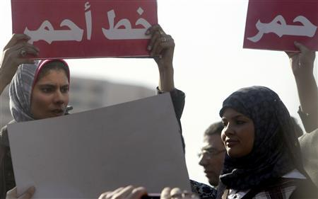 Samira Ibrahim (R) attends a protest against military council violations and virginity tests against females at Tahrir Square in Cairo, December 27, 2011. The banner reads ''Red line''. REUTERS/Amr Abdallah Dalsh