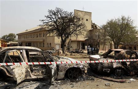 A security barrier marks the scene of a car bomb explosion at  St. Theresa Catholic Church (background) at Madalla, Suleja, just outside Nigeria's capital Abuja, December 25, 2011.  REUTERS-Afolabi Sotunde