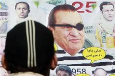 An Egyptian man stands in front of a poster depicting former Egyptian president Hosni Mubarak with his sons at Tahrir Square in Cairo, December 27, 2011.   REUTERS/Amr Abdallah Dalsh