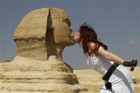 A tourist poses for a picture with the Sphinx at the Pyramids of Giza in Cairo October 19, 2011.    REUTERS/Jamal Saidi