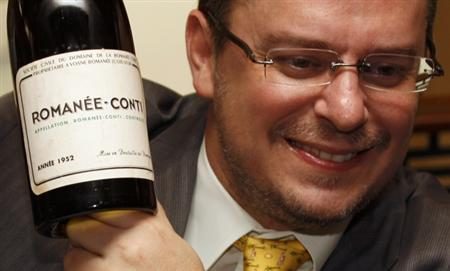 Chief Executive Officer of wine auctioneer Acker Merrall & Condit John Kapon poses with a Domaine Romanee Conti (DRC) wine bottle from 1952 at an auction preview in Hong Kong December 7, 2011. REUTERS/Bobby Yip
