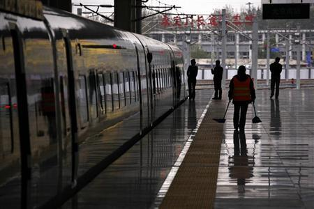 Train conductors and cleaners walk on a platform next to a CRH (China Railway High-speed) Harmony bullet train at the Beijing South railway station November 29, 2011.  REUTERS/David Gray