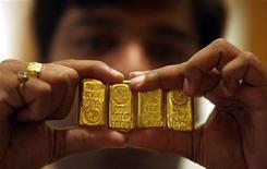 Продавец ювелирного магазина в Хидерабаде держит слитки золота 6 мая 2011 года. Цены на золото снижаются вместе с промышленными металлами и акциями на фоне опасений за рост мировой экономики и угрозы Ирана закрыть Ормузский пролив. REUTERS/Krishnendu Halder