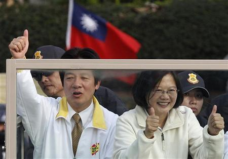 Democratic Progressive Party (DPP) Chairperson and presidential candidate Tsai Ing-wen (R) and a party official greet supporters from their vehicle during a campaign street rally for the 2012 presidential election in Tainan, southern Taiwan, December 27, 2011. REUTERS/Pichi Chuang