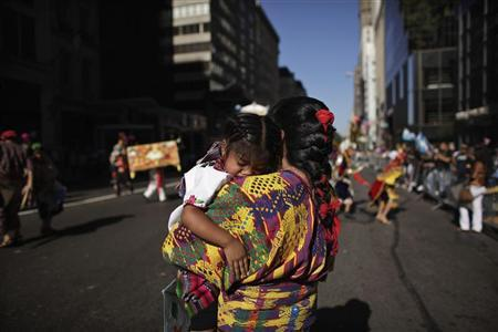 A reveller carries her sleeping child while taking part in the annual Hispanic Day Parade in New York October 9, 2011. REUTERS/Eduardo Munoz