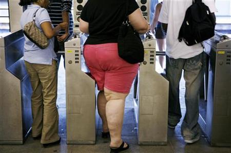Subway commuters walk through the turnstiles while leaving the U.S. Open in New York September 4, 2007. REUTERS/Lucas Jackson/Files