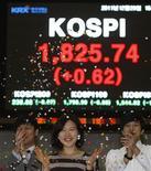 Сотрудники Сеульской фондовой биржи перед экраном со значением индекса KOSPI 29 декабря 2011 года. Фондовые рынки Азии закрылись в четверг снижением перед аукционом облигаций Италии и на фоне падения евро до минимума 10 лет к иене, но китайский и корейский рынки акций смогли показать рост. REUTERS/Kim Hong-Ji