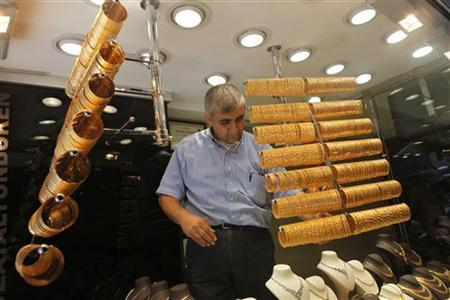 An employee arranges gold bangles at a jewellery shop in Istanbul August 23, 2011. REUTERS/Murad Sezer/Files