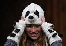 """Работница зоопарка Эдинбурга в шапке и перчатках в виде панды. Фотография сделана 29 ноября 2011 года. Британская телерадиовещательная корпорация """"Би-би-си"""" второй раз за последний месяц оказалась в центре гендерного скандала, включив панду в список из 12 женских лиц 2011 года. REUTERS/David Moir"""