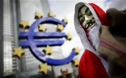 Участник акции протеста в костюме Санта Клауса стоит на фоне памятника евро во Франкфурте-на-Майне 24 декабря 2011 года. Евро в четверг рухнул до 10-летнего минимума к иене и самого низкого значения за 15 месяцев к доллару из-за опасений долгового кризиса еврозоны, так как доходность итальянских облигаций осталась очень высокой. REUTERS/Kai Pfaffenbach