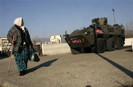A woman passes by an Austrian KFOR armoured vehicle guarding the main bridge in the ethnically divided town of Mitrovica, November 29, 2011.  REUTERS/HAZIR REKA