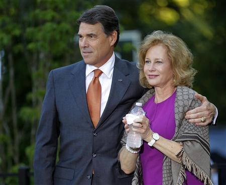 Republican presidential candidate Texas Governor Rick Perry (L), stands with his wife Anita, as he is introduced at a house party in Greenland, New Hampshire, in this August 13, 2011 photograph.  REUTERS/Brian Snyder