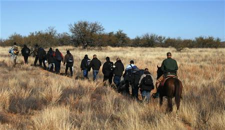U.S. Border Patrol agent Jim Weygand leads a group of arrested illegal immigrants through the Altar Valley, Arizona January 9, 2008.   REUTERS/Tim Gaynor