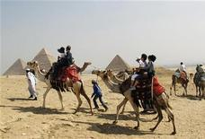 Tourists ride on camels as they visit the Pyramids of Giza in Cairo October 19, 2011.   REUTERS/Jamal Saidi