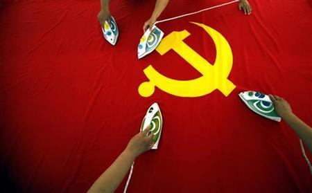 Workers use electric irons to smooth out a Communist Party of China flag on a table at the Beijing Jingong Red Flag factory located on the outskirts of Beijing June 28, 2011.  REUTERS/David Gray