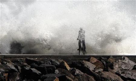 A man is drenched by a large wave during high tide as he cycles past at a fishing harbour in Chennai December 28, 2011. REUTERS/Babu