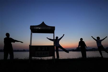 People exercise by a lake in Yangon at sunrise December 3, 2011.    REUTERS/Damir Sagolj