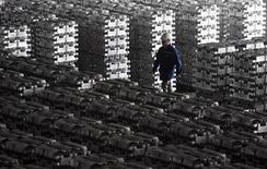 Рабочий Хакасского алюминиевого завода в Саяногорске проходит мимо рядов алюминиевых чушек 20 июня 2009 года. Российские металлурги и производители удобрений воспользовались вернувшимся в 2011 году финансовым кризисом для пересмотра стратегии, выплаты дивидендов и попыток улучшить ликвидность. REUTERS/Sergei Karpukhin