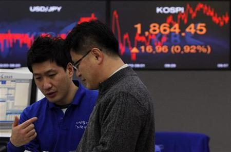 Foreign currency dealers from the Korea Exchange Bank (KEB) are seen in front of a monitor displaying the current Korea Composite Stock Price Index (KOSPI) at the KEB in Seoul December 23, 2011. Seoul shares rose on Friday, encouraged by signs of economic recovery in the U.S. following a string of positive data and easing global liquidity concerns. REUTERS/Kim Hong-Ji