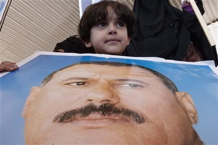 A boy carries a poster of Yemen's outgoing President Ali Abdullah Saleh during a rally to show support for Saleh in Sanaa December 30, 2011. REUTERS/Mohamed al-Sayaghi