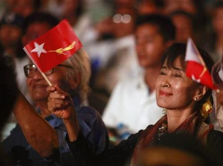 Myanmar's pro-democracy leader Aung San Suu Kyi waves her party flag as she watches a charity music show, organized by National League for Democracy (NLD) party, at Myanmar Convention Center in Yangon December 30, 2011. REUTERS/Soe Zeya Tun