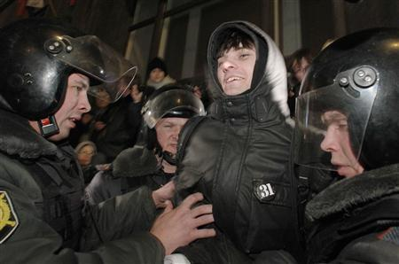 Police officers detain an activist during a protest rally defending Article 31 of the Russian constitution, which guarantees the right of assembly, in Moscow December 31, 2011.   REUTERS/Anton Golubev