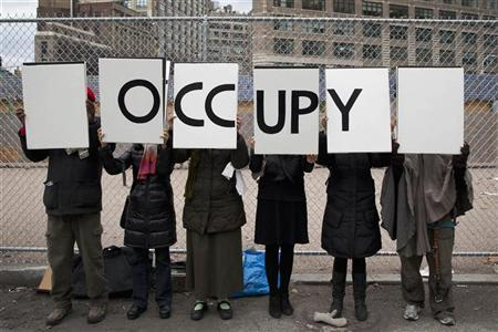 Protesters affiliated with the Occupy Wall Street movement stand with signs outside Duarte Square in New York, December 17, 2011. REUTERS/Andrew Burton