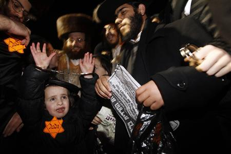 Ultra-Orthodox Jewish demonstrators look at a boy (low L) wearing a cloth cap and a yellow Star of David inscribed with ''Jude'', Jew, in German, sewn on his jacket as he raises his hands during a protest in Jerusalem's Mea Shearim neighbourhood December 31, 2011. REUTERS/Baz Ratner