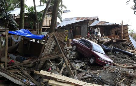 Typhoon Washi survivors rest in a makeshift shelter on New Year's day, near a car swept by rampaging floodwaters, in the southern Philippines city of Iligan on Mindanao island January 1, 2012. REUTERS/Erik De Castro