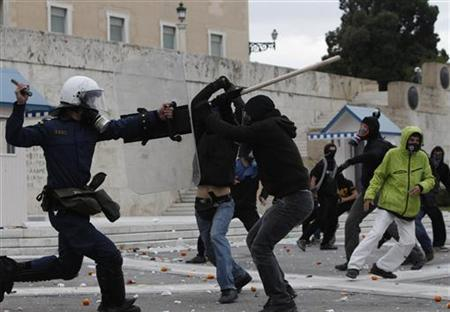 High school students clash with a policeman during riots in Athens December 6, 2011.  REUTERS/John Kolesidis