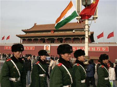 Chinese paramilitary policemen walk past an Indian flag in front of Tiananmen Gate in Beijing January 13, 2008. India's foreign ministry complained to Beijing at a high level on Monday, saying a diplomat was denied medicine to control severe diabetes and collapsed while offering consular assistance to two Indian citizens on trial in China's Yiwu city. REUTERS/Grace Liang/Files